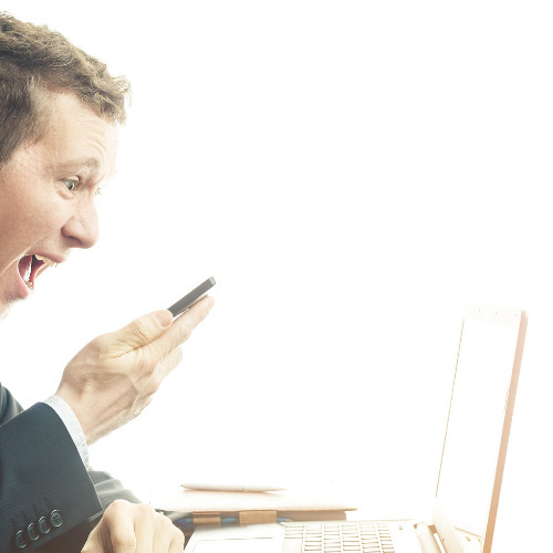 A Man yelling into his mobile phone while sitting infront of a laptop