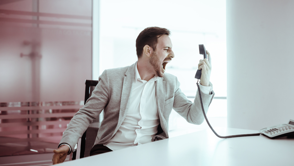 A man in his office yelling into a phone while sitting at his desk