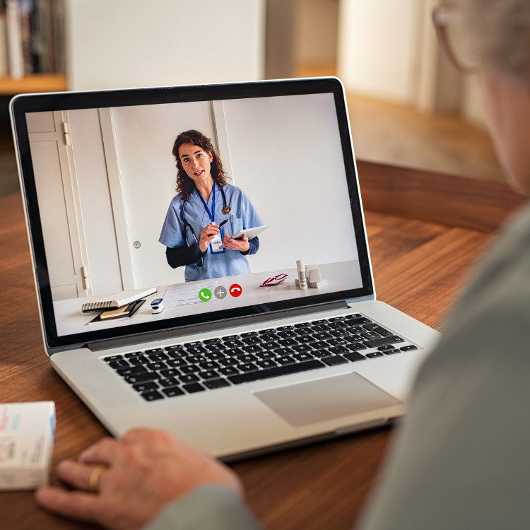 An elderly person using a laptop to video chat with their healthcare provider